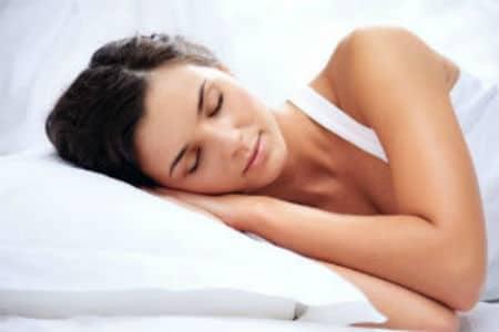 A woman lies facing us asleep with her hands under her head.